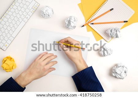 hands of a man thinking about idea with sheet of paper and pencil  - stock photo