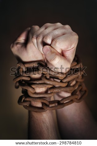 Hands of a man with a rusty chain around the wrists. Short depth of field, the sharpness is in the fist. - stock photo
