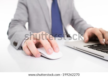 Hands of a man working with laptop on table