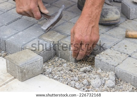Hands of a manual worker laying concrete brick pavers. - stock photo