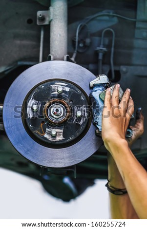 Hands of a mechanic install brake lining onto a car disc brake