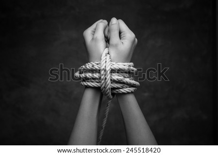 Hands of a missing kidnapped, abused, hostage, victim woman tied up with rope in cage cell. - stock photo