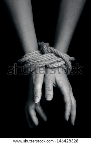 Hands of a missing kidnapped, abused, hostage, victim woman  tied up with rope in emotional stress and pain, afraid, restricted, trapped, call for help, struggle, terrified, locked in a cage cell. - stock photo
