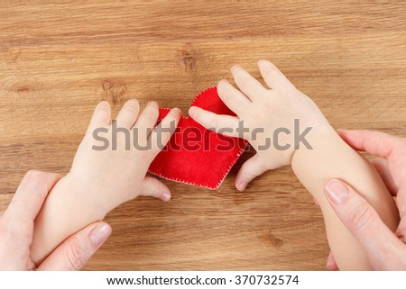 Hands of a mother and son holding a heart symbol. Concept of love, health and care - stock photo