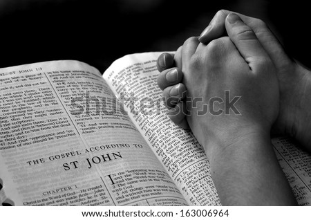 Hands of a person raised together in prayer with bible - stock photo