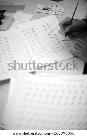 Hands of a person writing letters in calligraphy  - stock photo