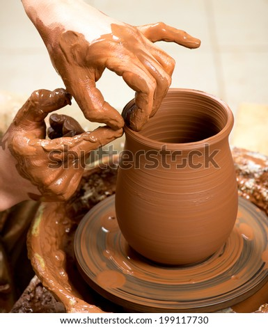 hands of a potter, creating an earthen jar - stock photo
