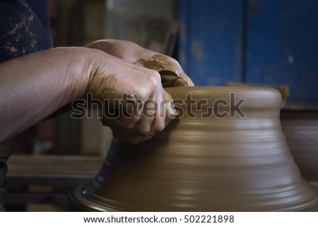 hands of a potter, creating an earthen jar on the wheel, circle
