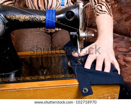 Hands of a seamstress at the sewing machine - stock photo