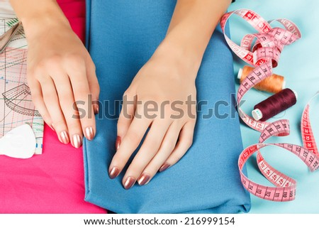 hands of a seamstress at work - stock photo