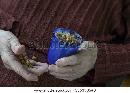 hands of a senior woman holding chickpeas and boza which is beverage made from hemp seed. - stock photo