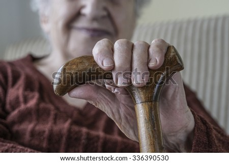 hands of a senior woman holding stick