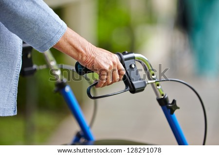 Hands of a senior woman on the handles of a walker - stock photo
