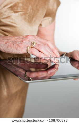 Hands of a senior woman using a tablet. Studio shot on grey background.