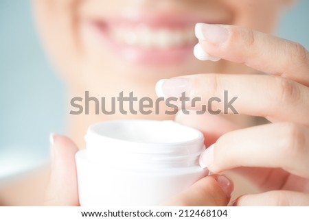 Hands of a woman about to apply face cream. - stock photo