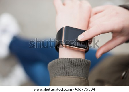 Hands of a woman browsing her trendy smart wrist watch. This new digital accessory lets you always stay connected to internet and social media networks from anywhere you want.