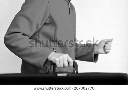 Hands of a woman carry travel suitcase against white background with copy space. Concept photo of travel, vacation, holiday, destination, tourism, traveler, tourist.(BW) - stock photo