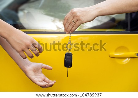 hands of a woman giving car keys to a young boy, outdoor photo
