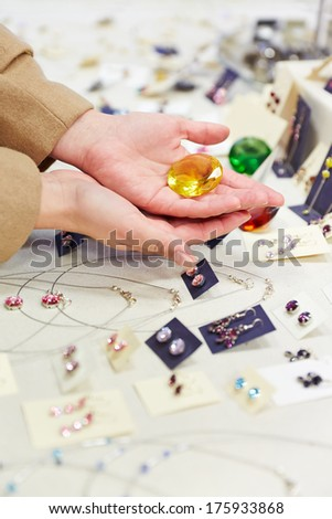 Hands of a woman holding a big gem at a jewelry store - stock photo