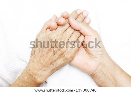 Hands of a woman holding the hand of an elderly woman.