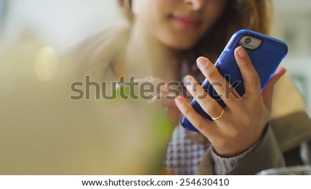 Hands of a woman using a mobile cell phone indoors - stock photo