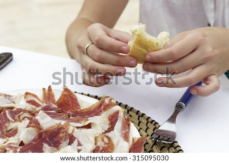 Hands of a woman with a bread slice while eats iberian ham