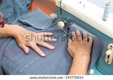hands of a woman working in sewing machine / woman sewing - stock photo