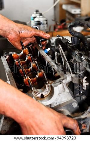 Hands of a worker repairing broken engine - stock photo