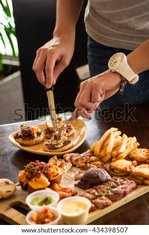 Hands of a young testing a mixed Grilled meat with fries, smoken cheese, beans and vegetables on wood table