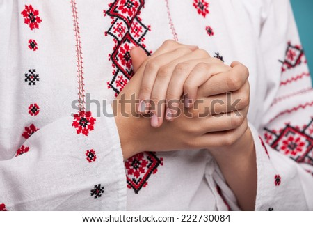 Hands of a young woman in the Ukrainian national clothes. Embroidered shirt - stock photo