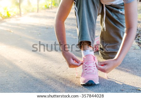 Hands of a young woman shoelace pink and pink sneakers. Shoes standing on the pavement of stones and sand. Photographed close-up. - stock photo