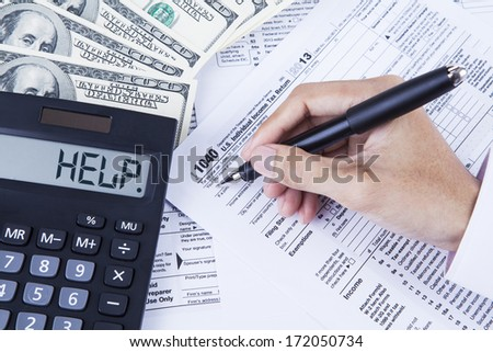 Hands of accountant filling the tax forms - stock photo