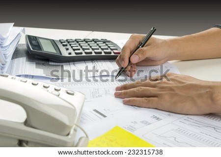 Hands of accountant with calculator and pen. Accounting background. - stock photo