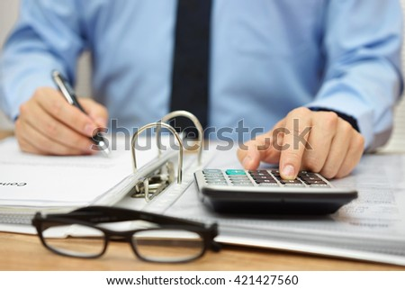 Hands of accountant with calculator,documentation and pen. Accounting concept - stock photo