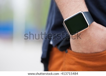 Hands of african black guy wearing trendy smart watch.Modern gadget that lets you always stay connected to internet,social media from everywhere.Macro close up on wrist watches. - stock photo