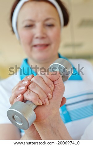 Hands of aged woman doing physical exercise with barbells - stock photo
