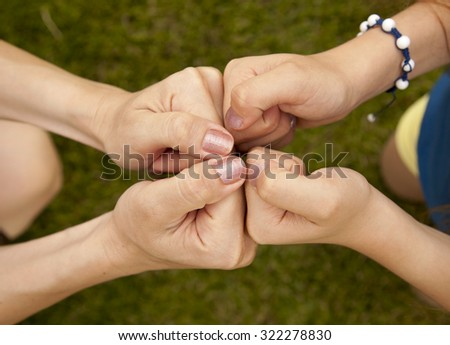 Hands of an adult and a child making a symbolic sign of being friends on green grass background in summertime. - stock photo