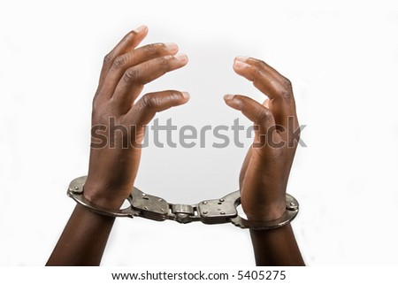 Hands of an African American woman handcuffed - stock photo