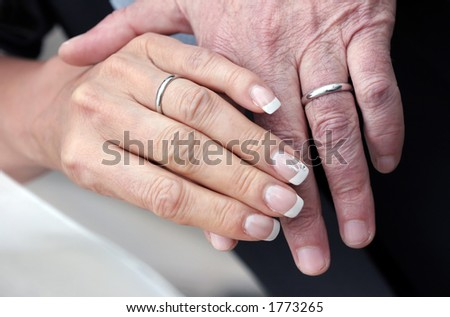 Hands of an aged couple who still wear their wedding-rings as the sign of their togetherness.