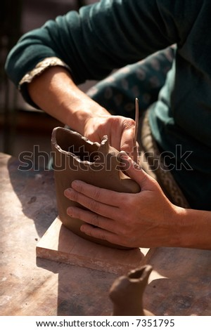 hands of an artist shaping a vase
