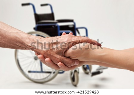 Hands of an elderly man holding the hand of a woman on wheelchair background - stock photo