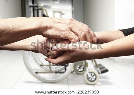 Hands of an elderly man holding the hand of a younger woman on wheelchair background - stock photo