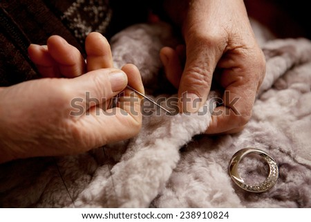 Hands of an elderly woman for sewing close-up