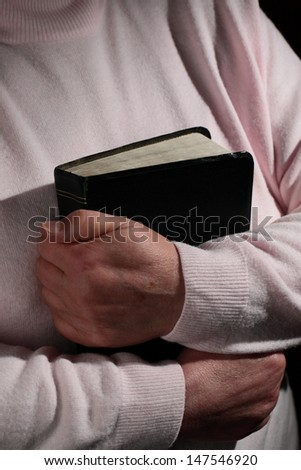 Hands of an elderly woman holding a Bible close to her body under dramatic lighting. - stock photo