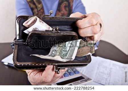 Hands of an elderly woman holding open the wallet - stock photo