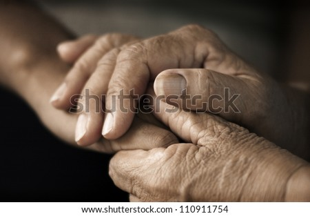 Hands of an elderly woman holding the hand of a younger woman. Lots of texture and character in the old ladies hands. - stock photo