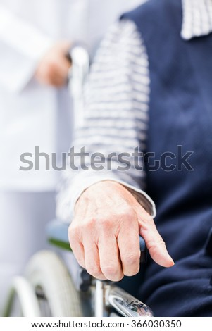 Hands of an elderly woman resting on the wheelchair