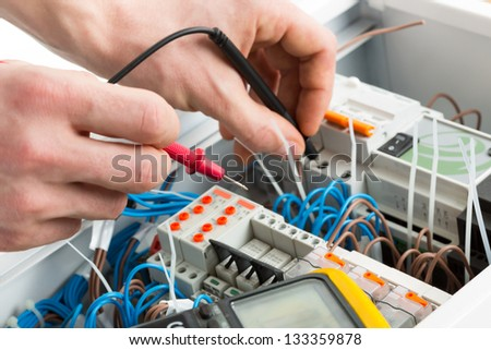 Hands of an electrician with multimeter probe at an electrical switchgear cabinet - stock photo
