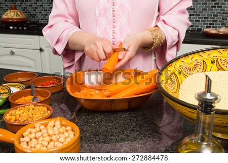 Hands of an immigrant woman in a modern European kitchen adding carrots to a traditional Moroccan tajine during Ramadan nights   - stock photo