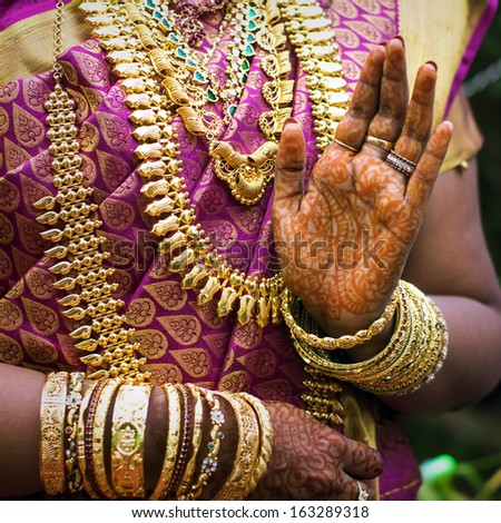 Hands of an Indian bride adorned with jewelery, bangles and painted with henna - stock photo